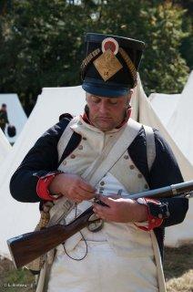 Reconstitution d'un bivouac des troupes napoléoniennes au château du Passage en Isère. Un soldat change le silex de son fusil