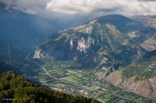La plaine de Bourg d'Oisans traversée par la Romanche. En arrière-plan, le village de Villard Reculas sur son plateau et la route en lacets de l'Alpe d'Huez