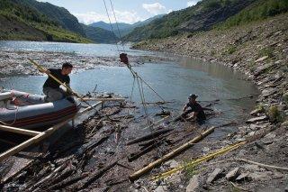 Lac du Chambon. Une équipe de débardeurs par câble sort les bois flottés du lac