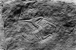 Gravure rupestre représentant un personnage avec une tête animale