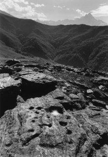 Pierre à cupules à Paesana, au fond le Mont Viso
